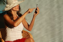 Woman in a straw hat writing SMS to mobile phone Stock Images