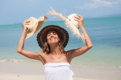 Woman with straw hats on a beautiful beach. Portrait of a happy woman with straw hats on a beautiful beach Stock Image