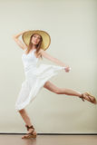 Woman in straw summer hat white dress jumping Stock Photo