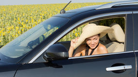 Woman in straw sun hat in car Stock Images
