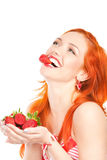 Woman with strawberry. Portrait of sexy redhead woman holding and biting strawberry Royalty Free Stock Photography