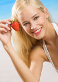 Woman with strawberry on beach Stock Photo