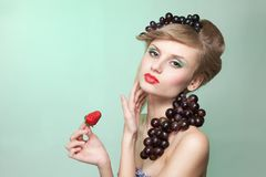 Woman with strawberry and bunch of grapes Royalty Free Stock Image