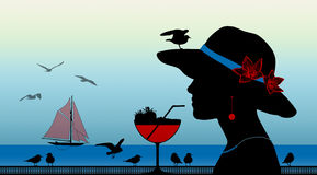 Woman with a strawberry cocktail next to the sea. Profile of a young woman drinking a strawberry cocktail with a seagull on her hat looking on the sunset above Stock Image