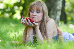 The woman and a strawberry handful Stock Photography