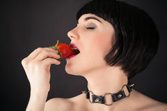 Woman with strawberry in mouth Stock Image