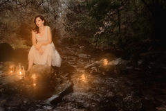 Woman in stream with candles Royalty Free Stock Photos