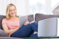 Woman Streams Music From Digital Tablet To Wireless Speaker Royalty Free Stock Photography
