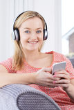 Woman Streams Music From Mobile Phone To Wireless Headphones Stock Photo