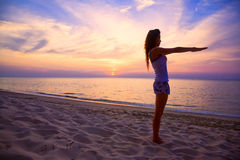 Woman streching arms on the beach. Woman stretching both arms relaxing on the beautiful sunset beach Royalty Free Stock Images