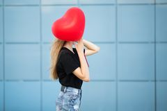 Woman in the street on a blue background. Red heart shaped ball. stock photos