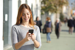 Woman in the street browsing a smart phone. Portrait of a beautiful casual woman in the street browsing a smart phone Royalty Free Stock Photos