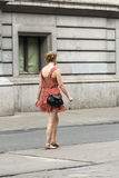 Woman in a street. BRUSSELS, BELGIUM - JULY 4, 2015: A woman wearing a short dress and a black bag, walk down one of the streets of the city Stock Photo