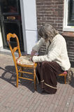 Woman on the street busy with chair braids Stock Photo