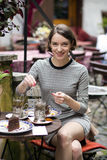 Woman at street cafe brews tea and smile. Woman at cafe brews tea and smile Royalty Free Stock Image