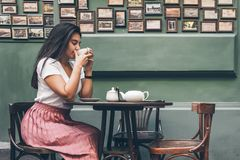 Woman in a street cafe dreanking tea. Attractive woman in a street cafe dreanking tea Royalty Free Stock Photography