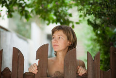 Woman on the street. Woman in the city near the wooden gate Royalty Free Stock Photography