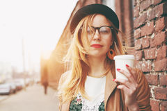 Woman in street drinking coffee Stock Photography