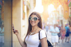 Woman on the street. With her phone Stock Photo