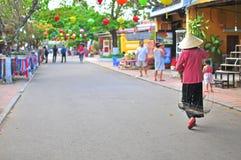 Woman in the street of Hoi An, Vietnam. HOI AN, VIETNAM - MARCH 15: Silhouette of a woman in the street of Hoi An old town, Vietnam on March 15, 2015. Hoi An is stock photography