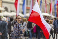 Woman on the street holding a flag of the Republic of Poland. Holiday. Royalty Free Stock Photo