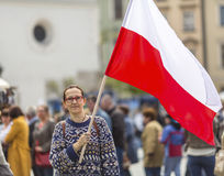 Woman on the street holding a flag of the Republic of Polish. Royalty Free Stock Photos