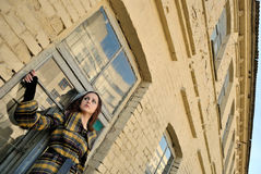Woman on street, low angle view. Young woman standing near an old rough building, low angle view Royalty Free Stock Images