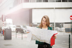 Woman on the street with a map Stock Images