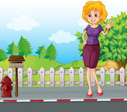 A woman at the street near the wooden mailbox Stock Photos