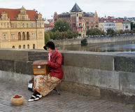 Woman with street organ on Charles Bridge in Prague. Royalty Free Stock Images