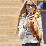Woman on street with smartphone Stock Image