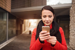Woman in the street texting with her mobile Stock Photos