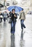 Woman on street with umbrella Stock Image