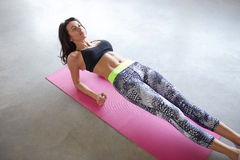 Woman strengthening stomach muscles. Beautiful young woman exercising and doing an elbow back plank to strengthen her stomach muscles. Above view Royalty Free Stock Images