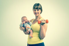 Woman strengthens with dumbbell after childbirth Royalty Free Stock Photo