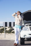 Woman stressed with car breakdown. Portrait stressed mature woman breakdown with car calling for service, assistance for help on mobile phone, with blue sky as Stock Image