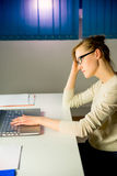 Woman stressed out about work. A woman in office is stressed out about her work Stock Image