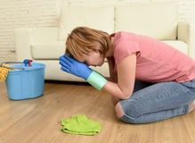 Woman stressed and tired cleaning the house washing the floor on her knees praying Royalty Free Stock Photography