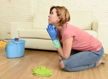 Woman stressed and tired cleaning the house washing the floor on her knees praying Royalty Free Stock Images