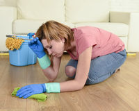 Woman stressed and tired cleaning the house washing the floor on her knees Stock Image