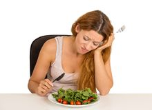 Woman stressed tired of diet restrictions. Young woman tired of diet restrictions deciding whether to eat healthy food craving sweet cookies sitting at table Stock Images