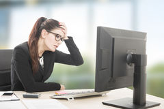 Woman stressed and tired. Young professional woman stressed and tired with headache sitting at office desk Royalty Free Stock Image