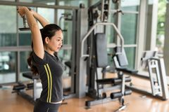 Woman stretch arms and hands by dumbbell. Fitness Asian woman stretch arms by dumbbell at gym with copy space for text. Healthy girl has intensive training and Royalty Free Stock Images