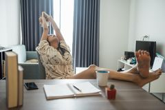 Woman stretch body during reading book. Beautiful Asian woman stretching hands and body during reading book. Girl leisure activity at working table in home Royalty Free Stock Photo