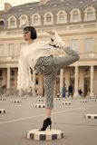 Woman stretch leg on square in paris, france. Girl in high heel shoes, fashionable clothes. Yoga, pilates, fitness, sport. Fashion, beauty, style lifestyle royalty free stock photography