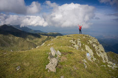 Woman with stretched arms in the mountains Stock Images