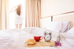 Woman stretched in bed room after the alarm clock and bread in t Royalty Free Stock Photos