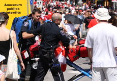 Woman on Stretcher in Crowded Street Stock Photo