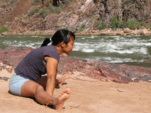Woman stretches. An Asian woman stretches on the beach by the Colorado River at the bottom of the Grand Canyon Stock Photography