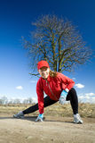 Woman stretches after cross country running Royalty Free Stock Photography